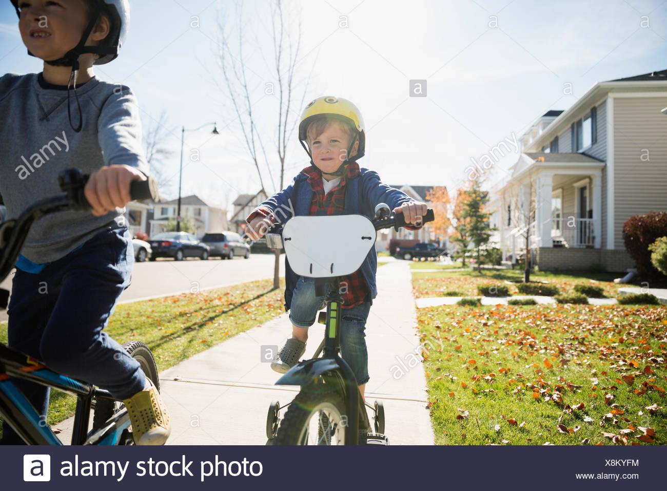 Les garçons faire du vélo sur les trottoirs du quartier d'automne Photo Stock