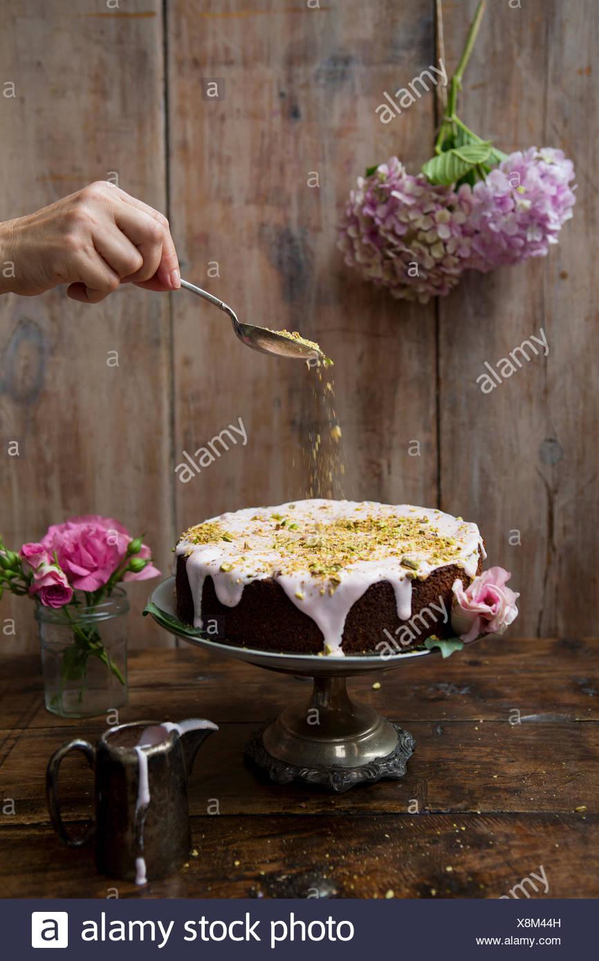 Pistache et Rose gâteau avec les écrous d'arrosage à la main Photo Stock