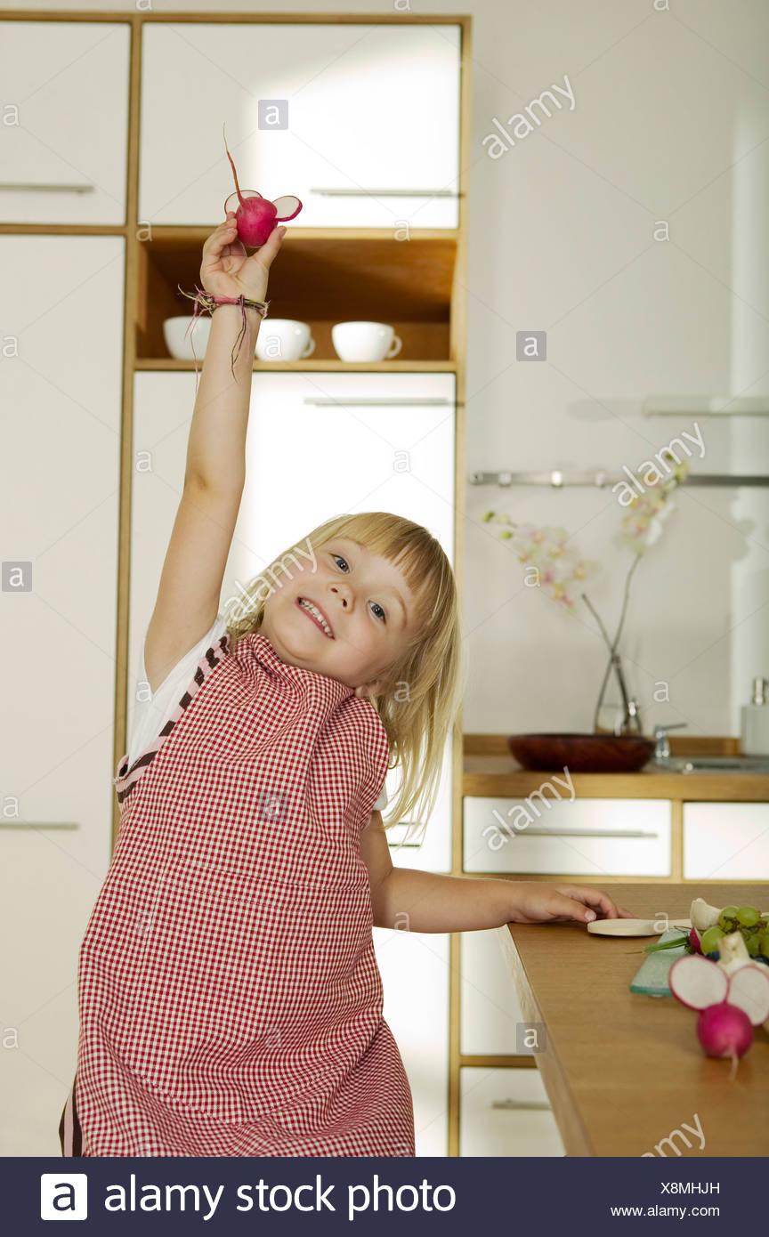 Girl (4-5) holding dans la cuisine, radis, close-up, portrait Photo Stock