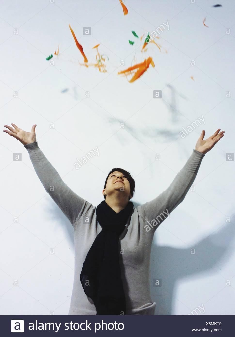 Jeune femme jetant contre les particules de Couleur Fond blanc Photo Stock