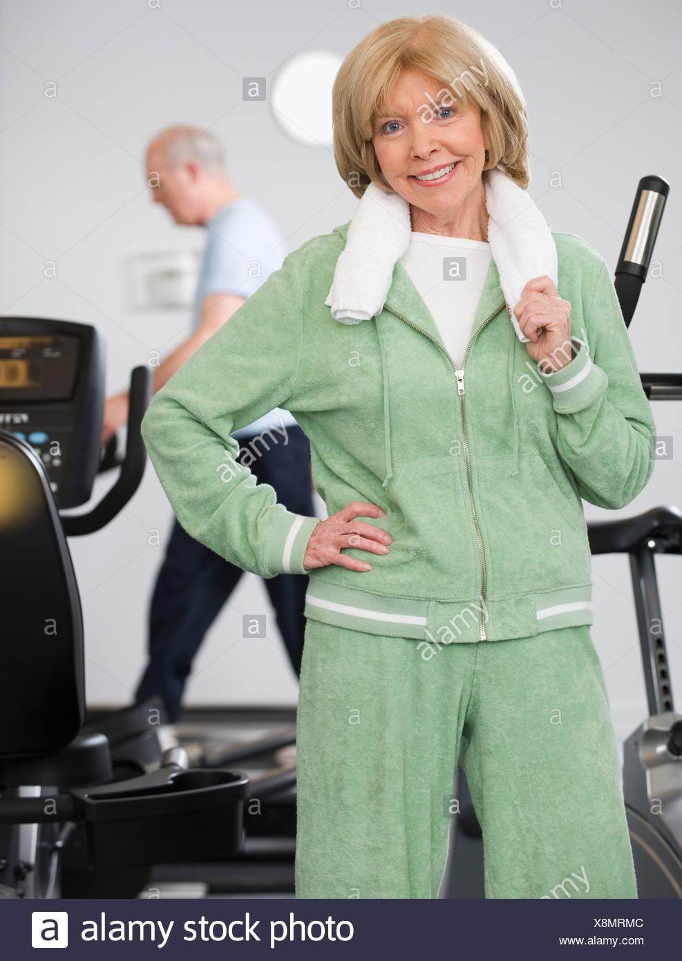 Senior woman à côté de machines d'exercice Photo Stock