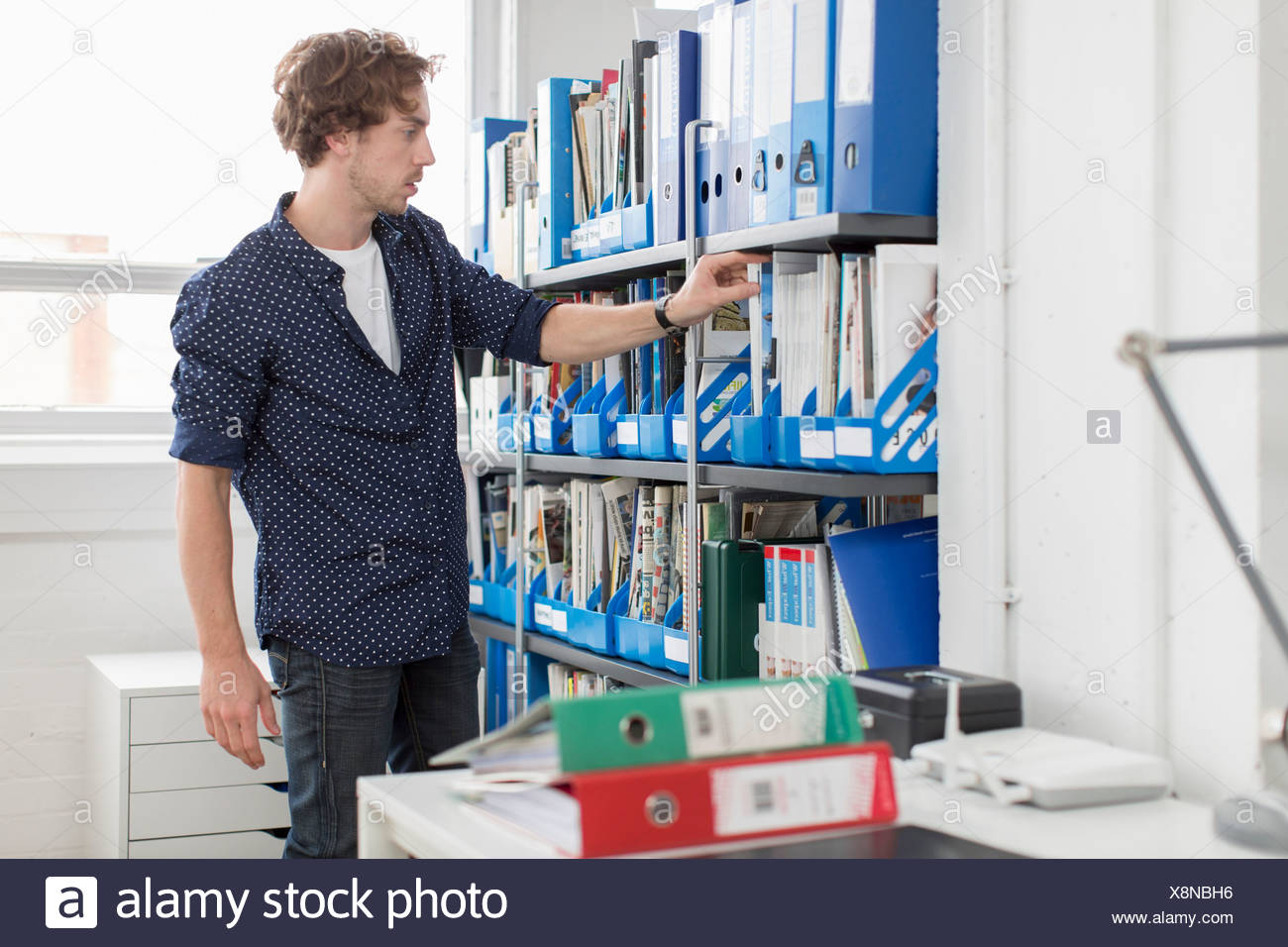 Les jeunes travailleurs de bureau prenant de la plate-forme de fichier Photo Stock