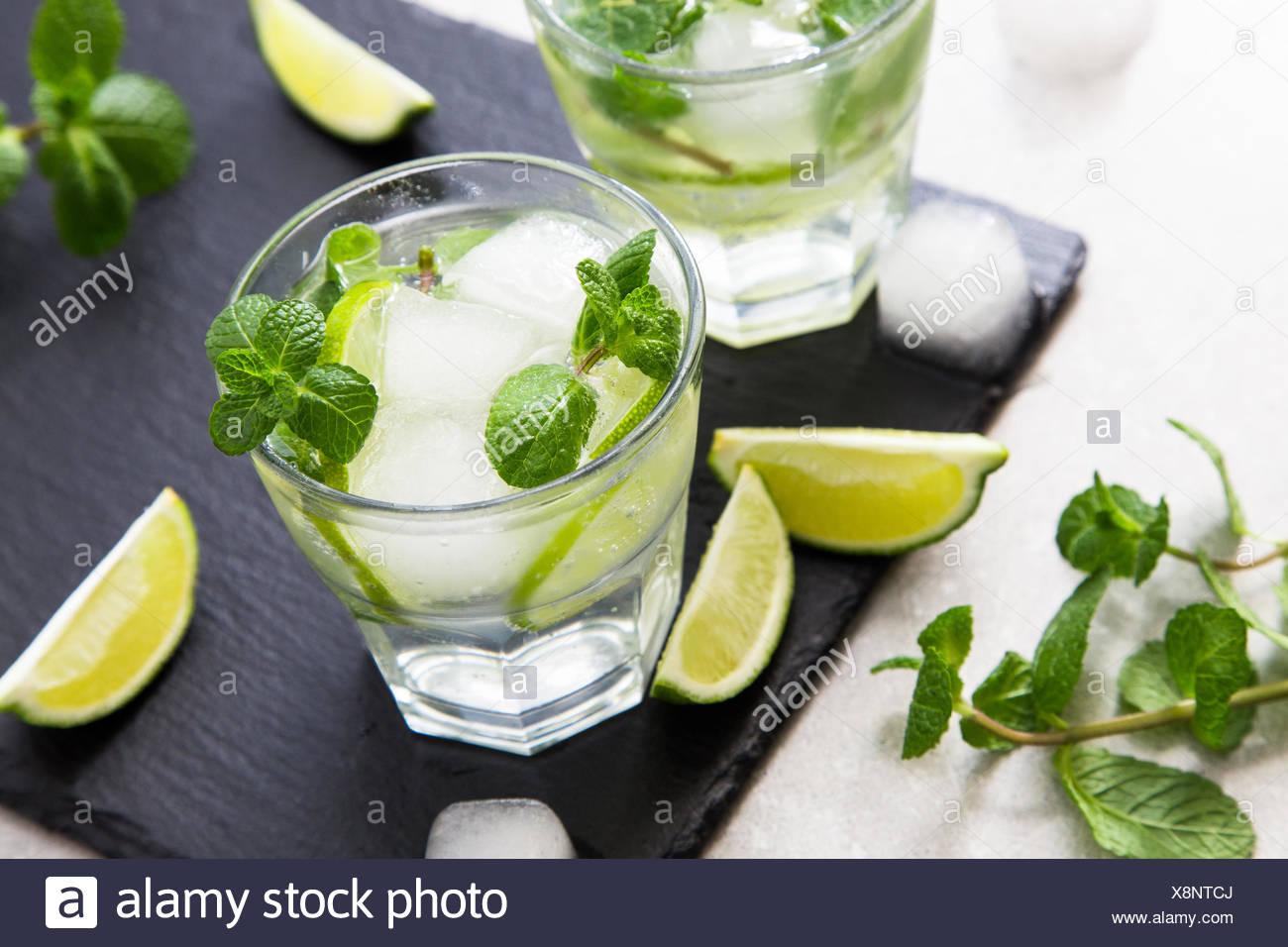 Rempli de limonade d'été mojito dans un verre sur un fond noir en ardoise et du conseil. Photo Stock