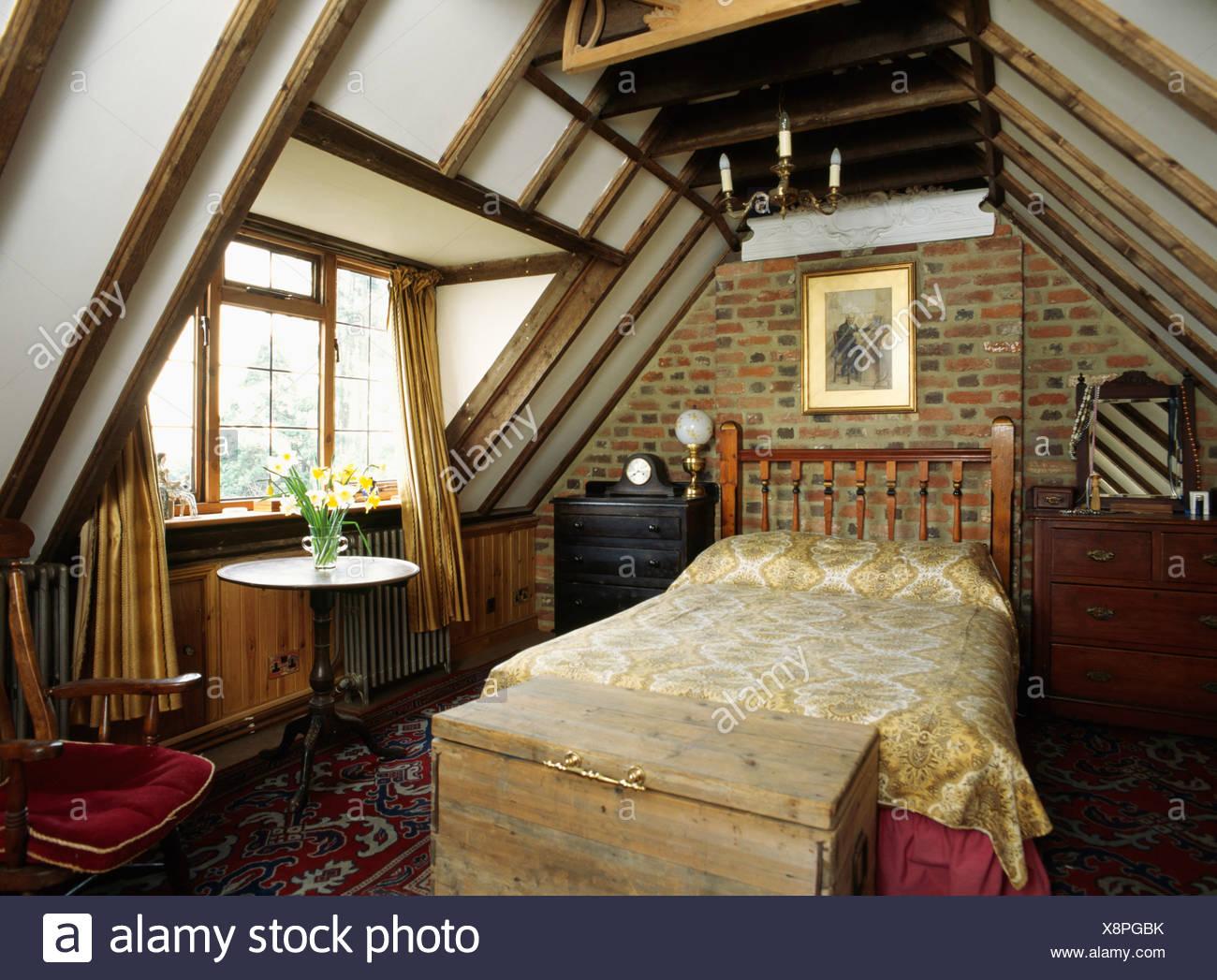 Coffre en bois en dessous de lit dans une chambre mansardée avec mur ...