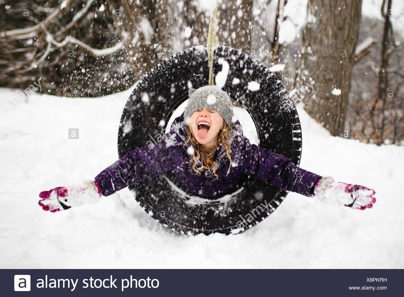 Fille jouant dans la neige sur balançoire pneu Photo Stock