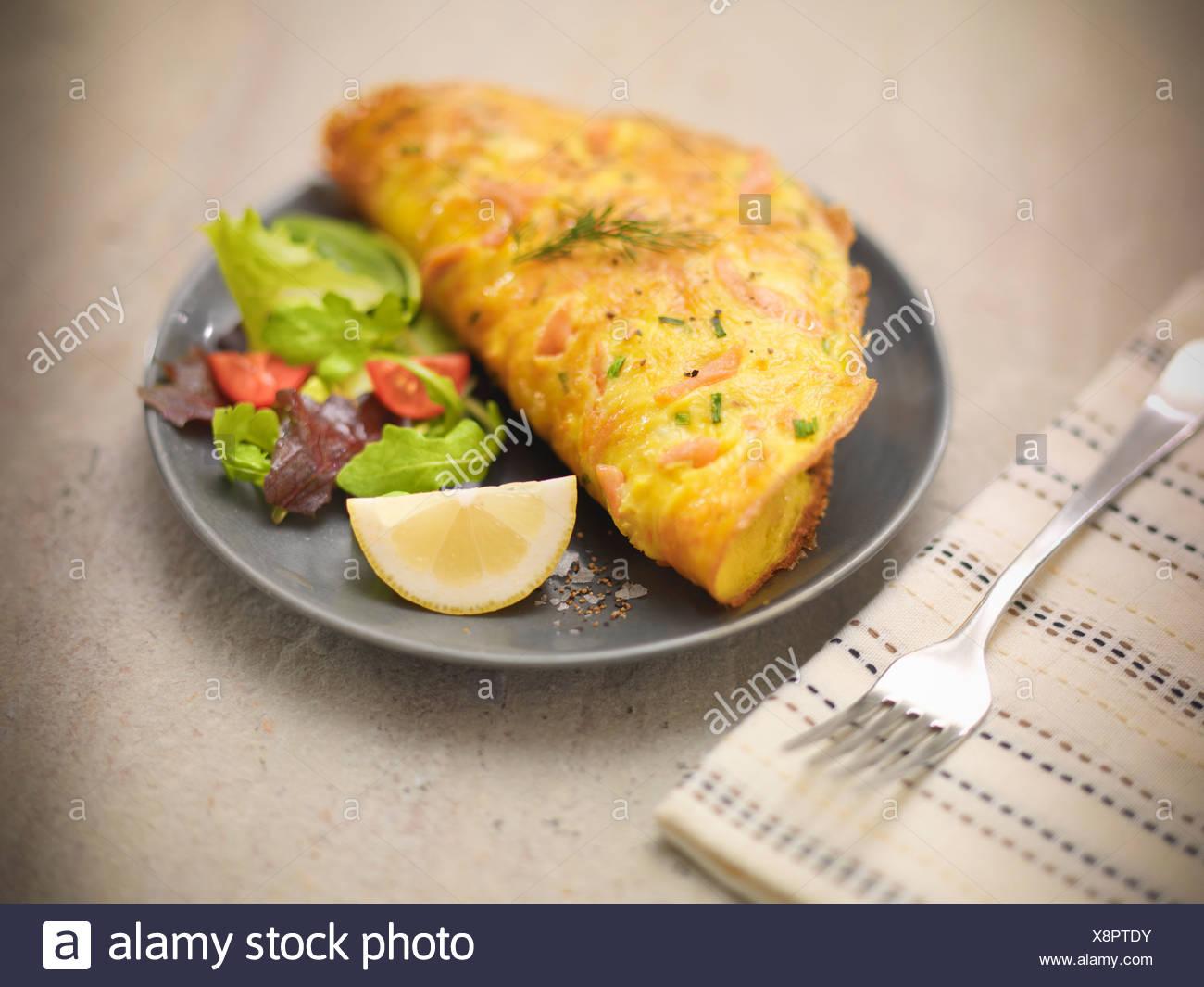 Plaque de base de l'omelette au saumon et salade Photo Stock