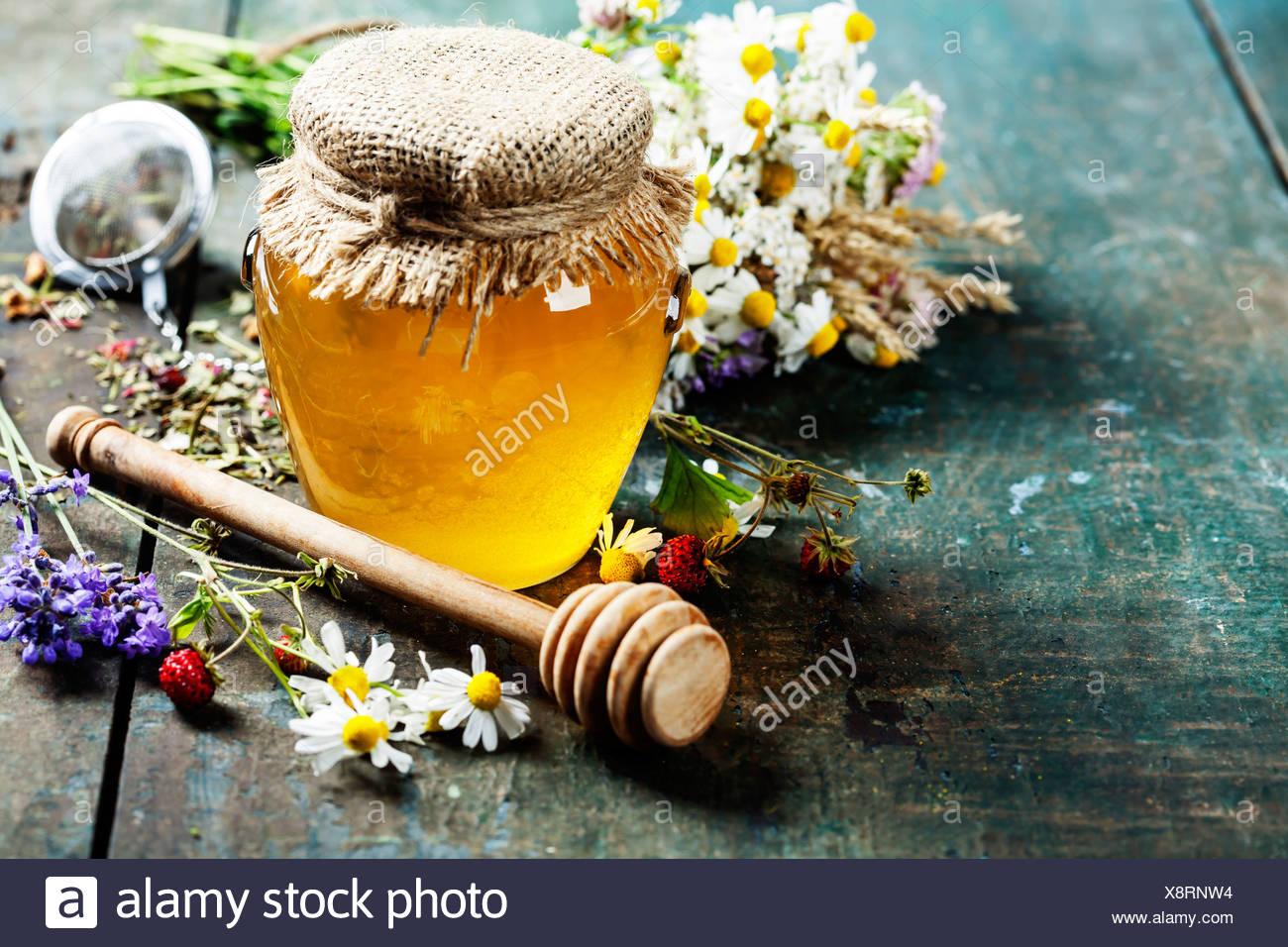 Le miel et le thé de fines herbes sur fond de bois - l'été, de la santé et de l'organic food concept Photo Stock