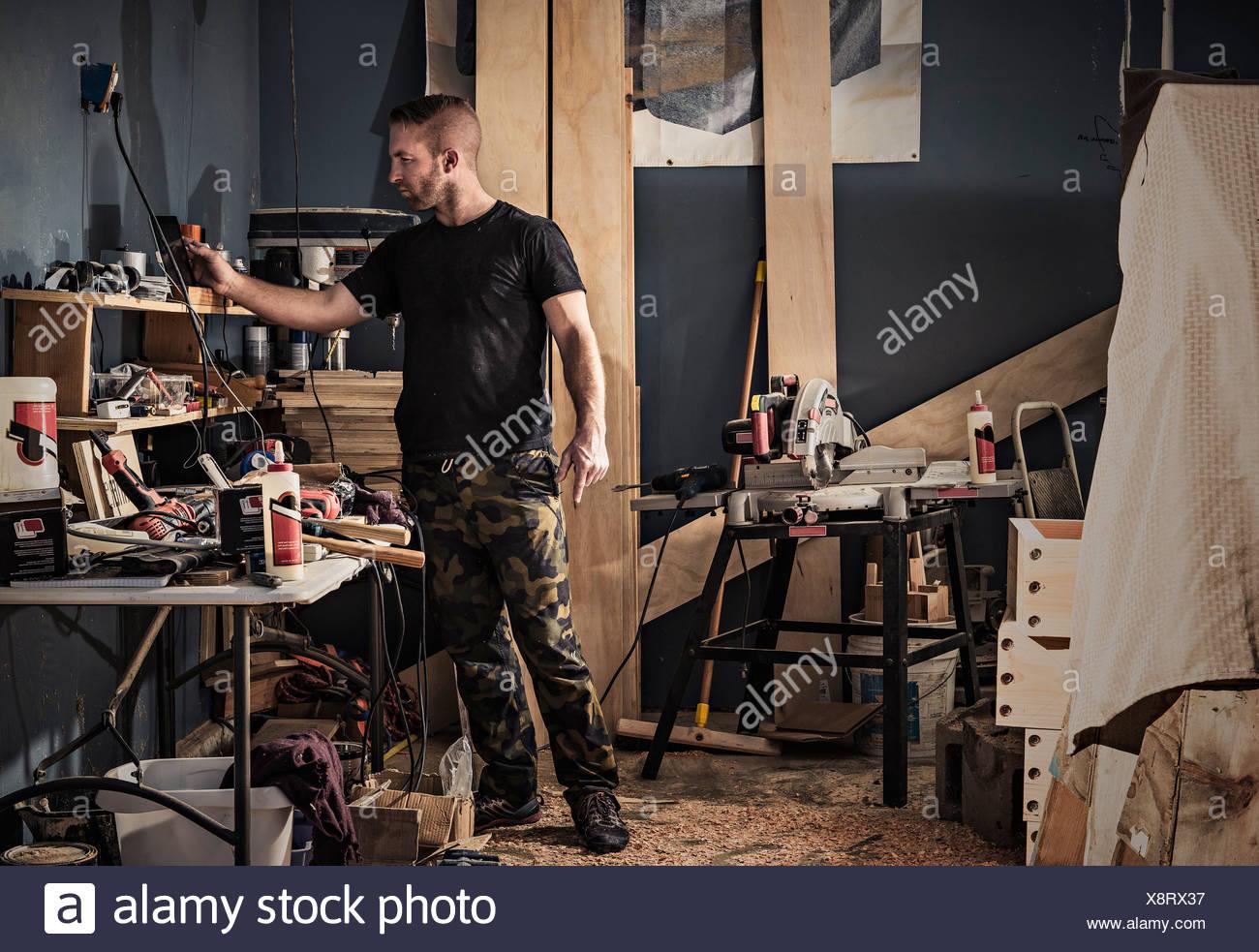 La recherche d'étagères dans Male carpenter workshop Photo Stock