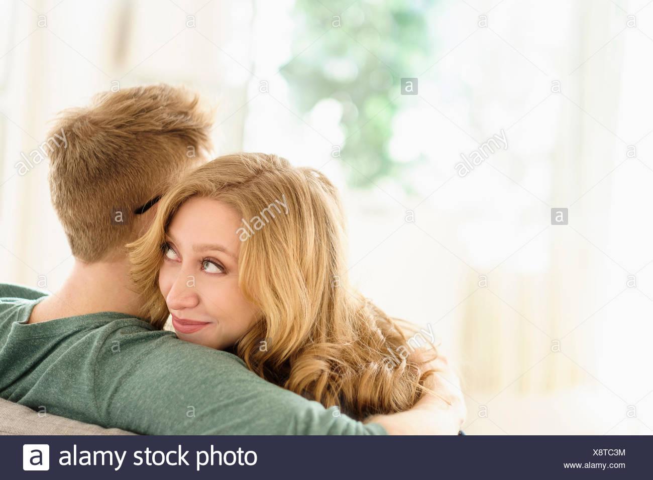 Jeune femme regardant par-dessus l'épaule de petit ami Photo Stock