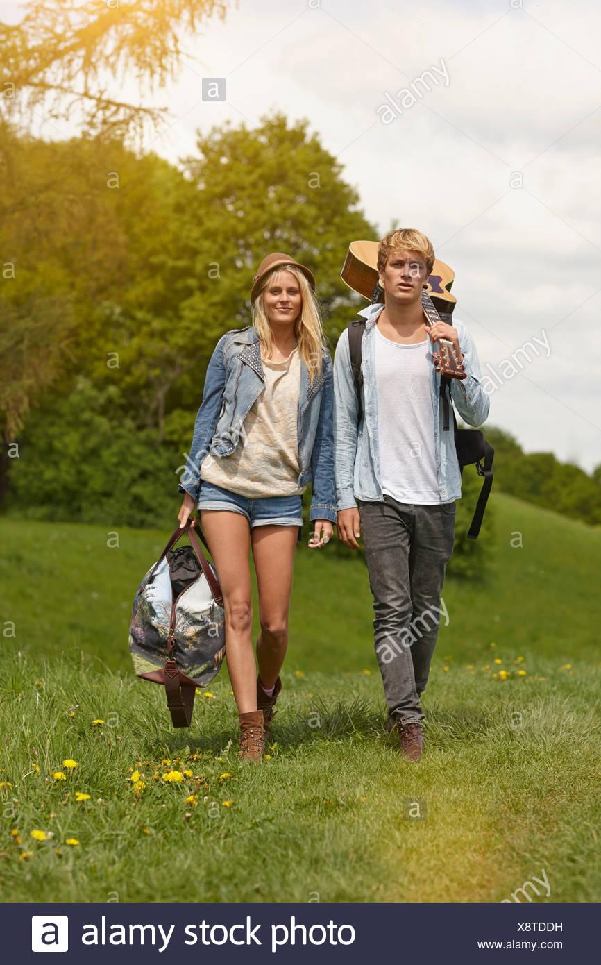 Jeune couple en train de marcher à travers champ avec guitare Banque D'Images