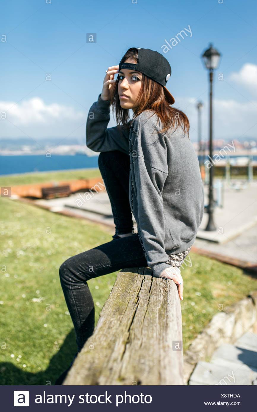 L'Espagne, Gijon, jeune femme assise sur poutre en bois Photo Stock