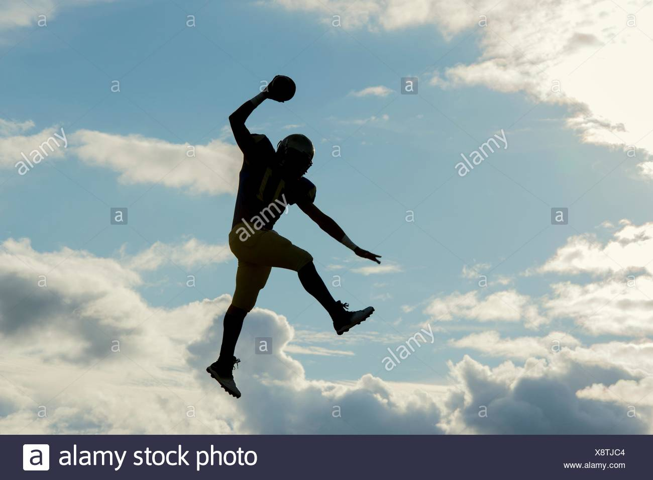 Teenage american football player, sautant avec balle, mid air Photo Stock