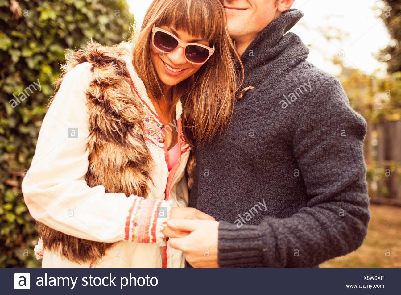 Couple holding hands laughing, cropped Photo Stock