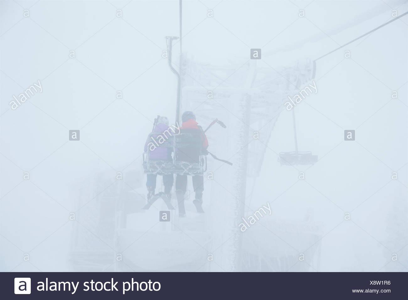 Frères et sœurs équitation le télésiège pour skier dans des conditions orageuses. Photo Stock