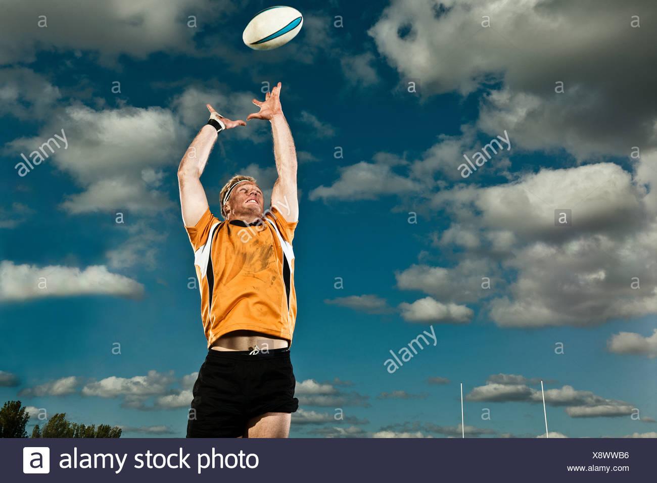 Joueur de Rugby en sautant jusqu'à attraper ball Photo Stock