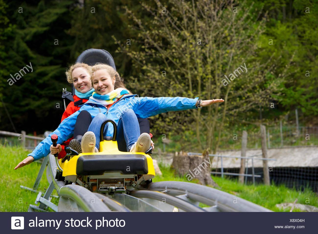 Les jeunes femmes sur une piste de luge d'été, dans le Steinwasenpark Oberried, Forêt-Noire, Bade-Wurtemberg, Allemagne Photo Stock