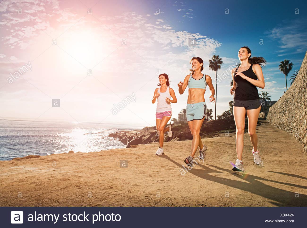 Les femmes adultes au milieu du jogging le long de falaise Photo Stock