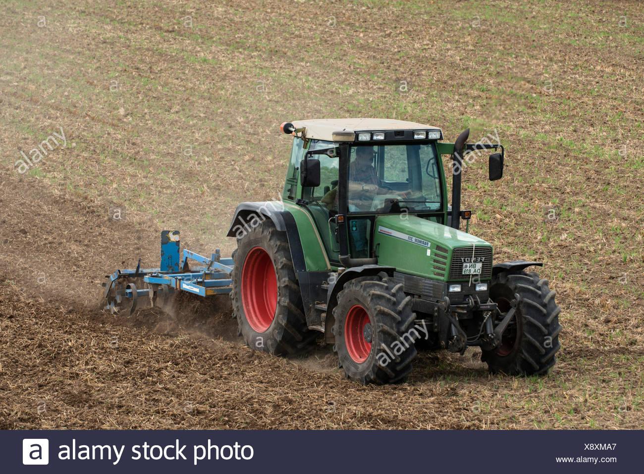 Tracteur avec un cultivateur sur les terres agricoles, PublicGround Photo Stock