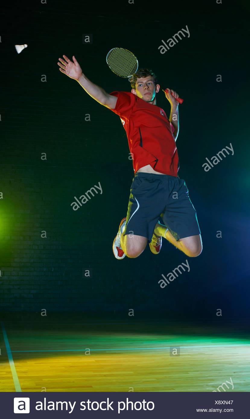 Jeune joueur de badminton masculin mi air sur cour Photo Stock