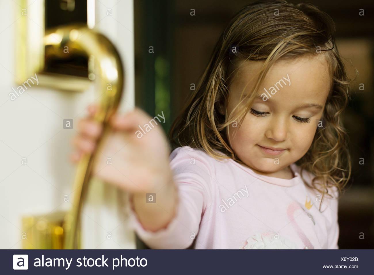 Female toddler opening door Photo Stock