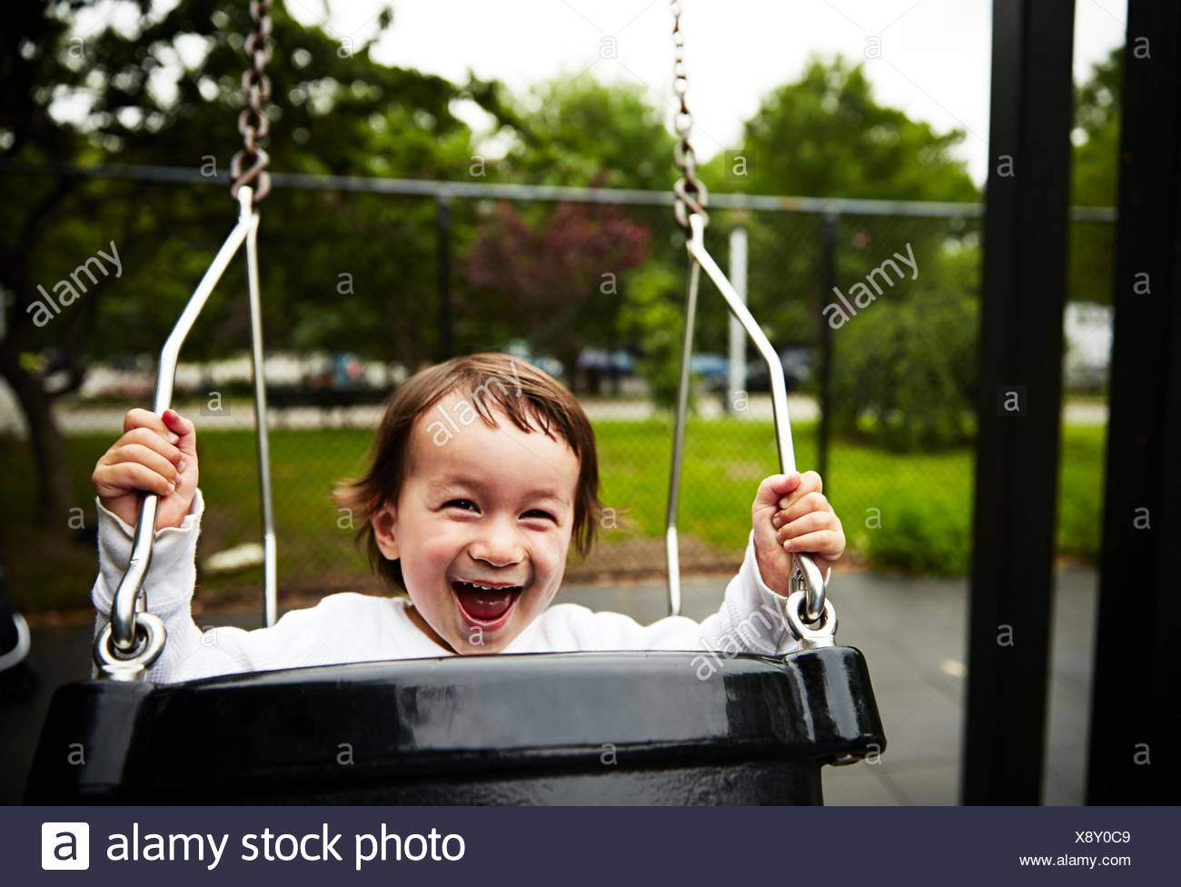 Boy playing on swing Photo Stock