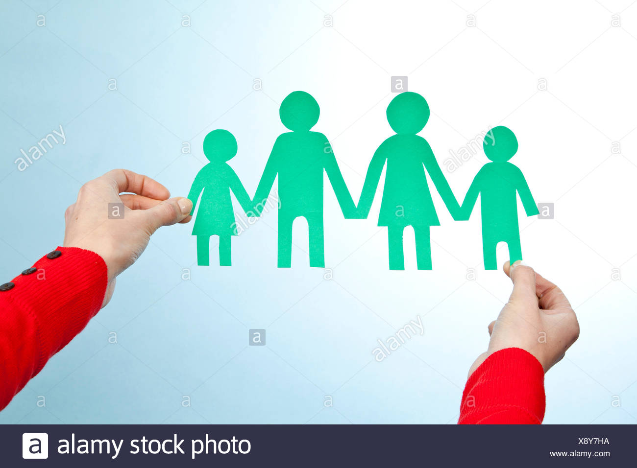 Hands holding paper cut out of family Photo Stock