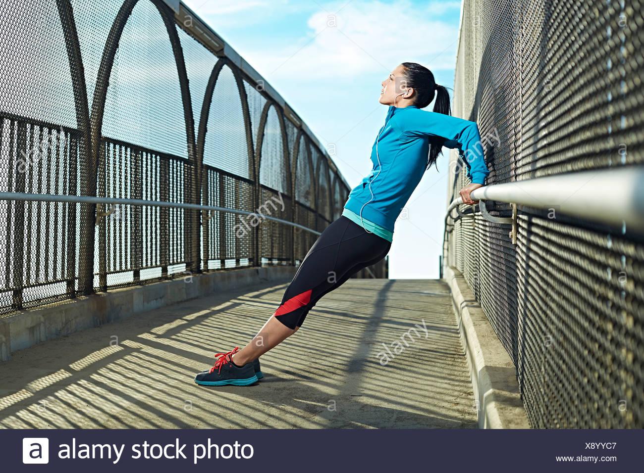 Mid adult woman stretching on bridge Photo Stock