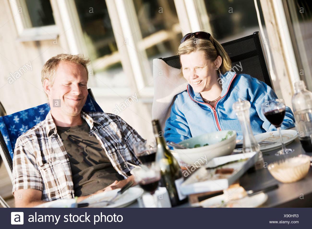 Content middle-aged couple having dinner sur le porche Photo Stock