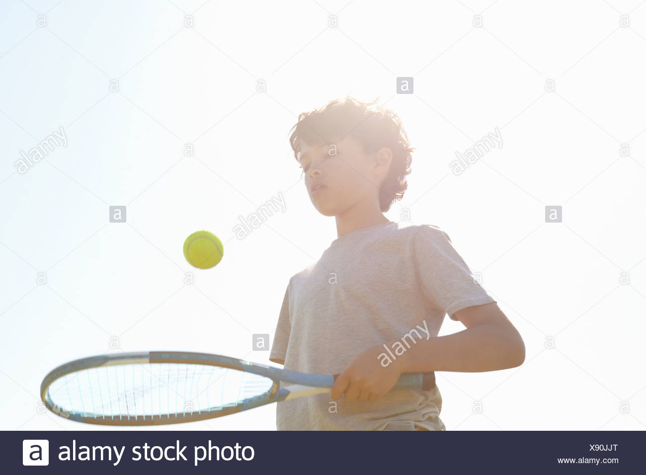 Garçon balle rebondissante sur raquette de tennis Photo Stock