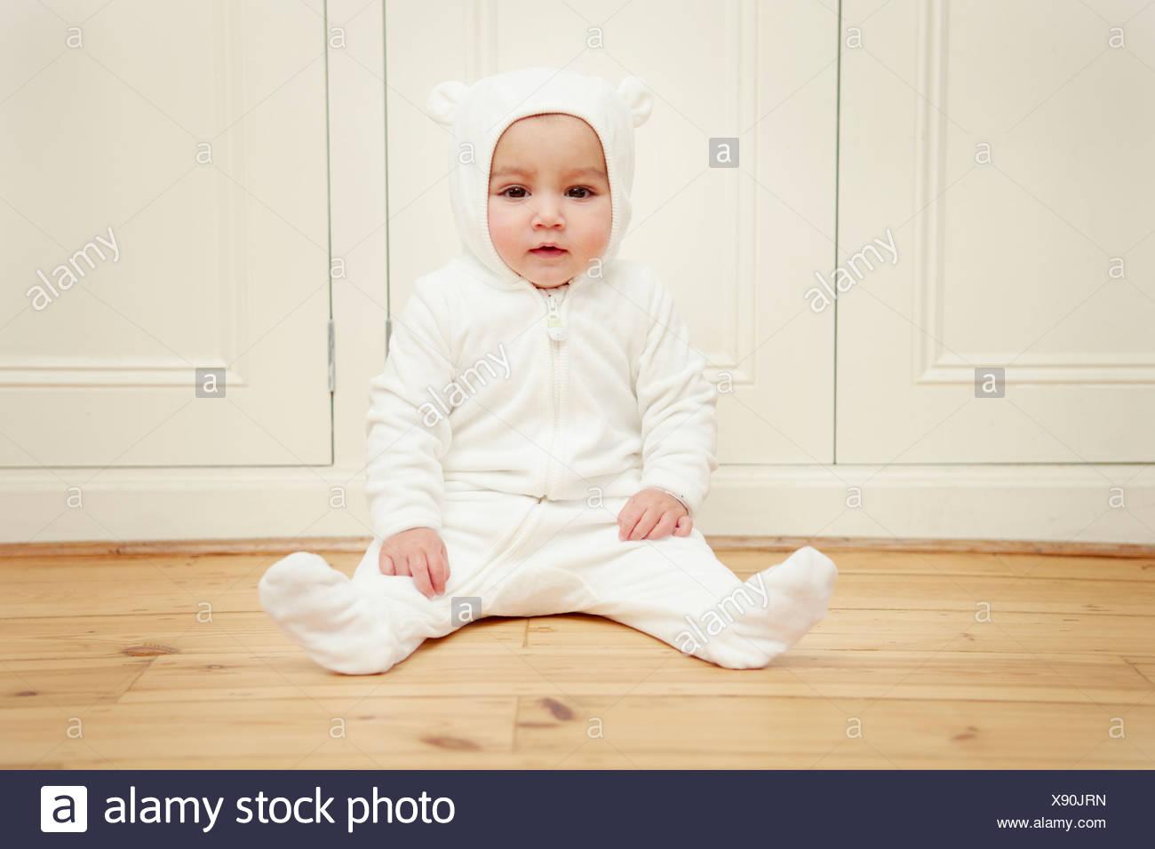 Baby sitting wearing bear babygro Photo Stock
