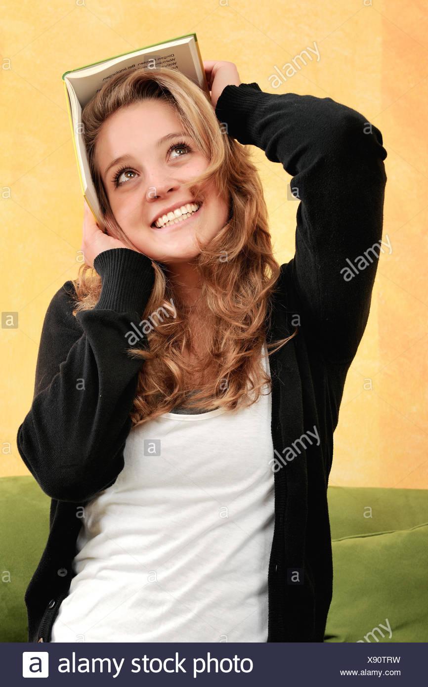 Schülerin, Studentin, Frau, Matura, Abiturientin, junge Frau, Lesen, Buch, Kopf, Witz, Witzig, humour, Euphorie, Begeisterung, Spaß, Reflexen, hübsch, lächeln, gemütlich, Spannung, Freizeit, Freude, zu Hause, Scherz, Jung, weiblich, adolescent, Pubertät, Amüsement, hobby, Bildung, Wissen, Klug, Intelligenz, Weiterbildung, Fortbildung, Wohnzimmer, canapé, Bett, Portrait, halten, Bildung, Lernen, Abschalten, Literatur, Lexikon, Wörterbuch, romain, l'enfer, Innenraum, allein, seul, solo, Sitzend, Lesespaß Orangefarben Sitzen,, Photo Stock