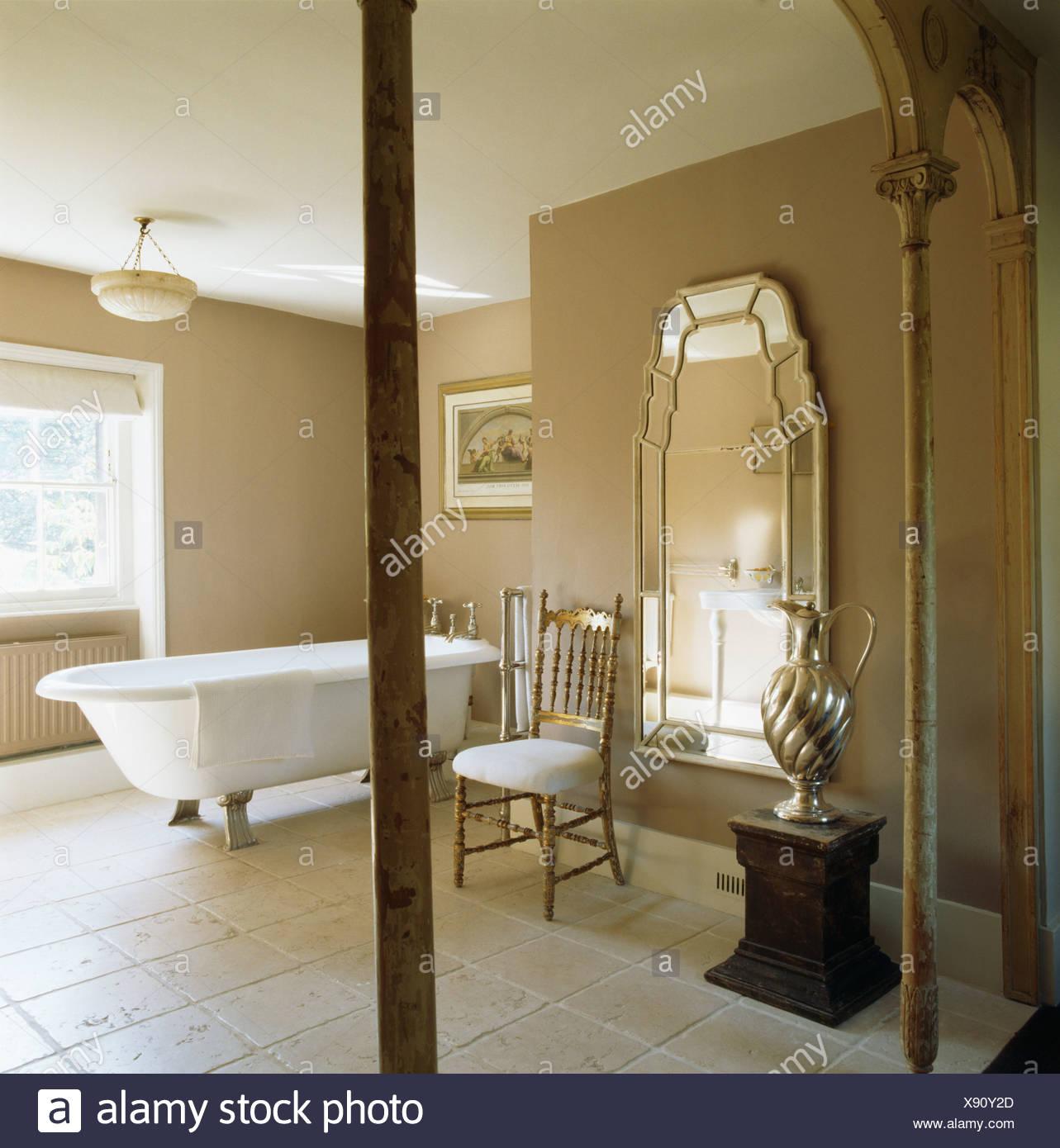 Grand Miroir Vénitien Et Une Baignoire Dans La Salle De Bain Beige Avec Un  Sol Calcaire
