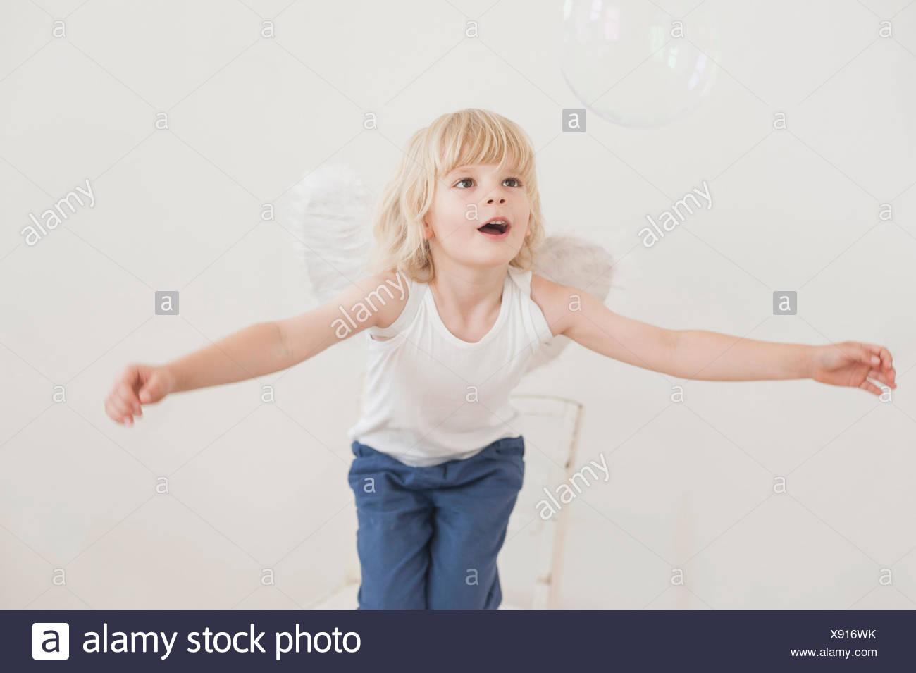 Portrait de petit garçon béant avec angle ailes regardant une bulle de savon Photo Stock