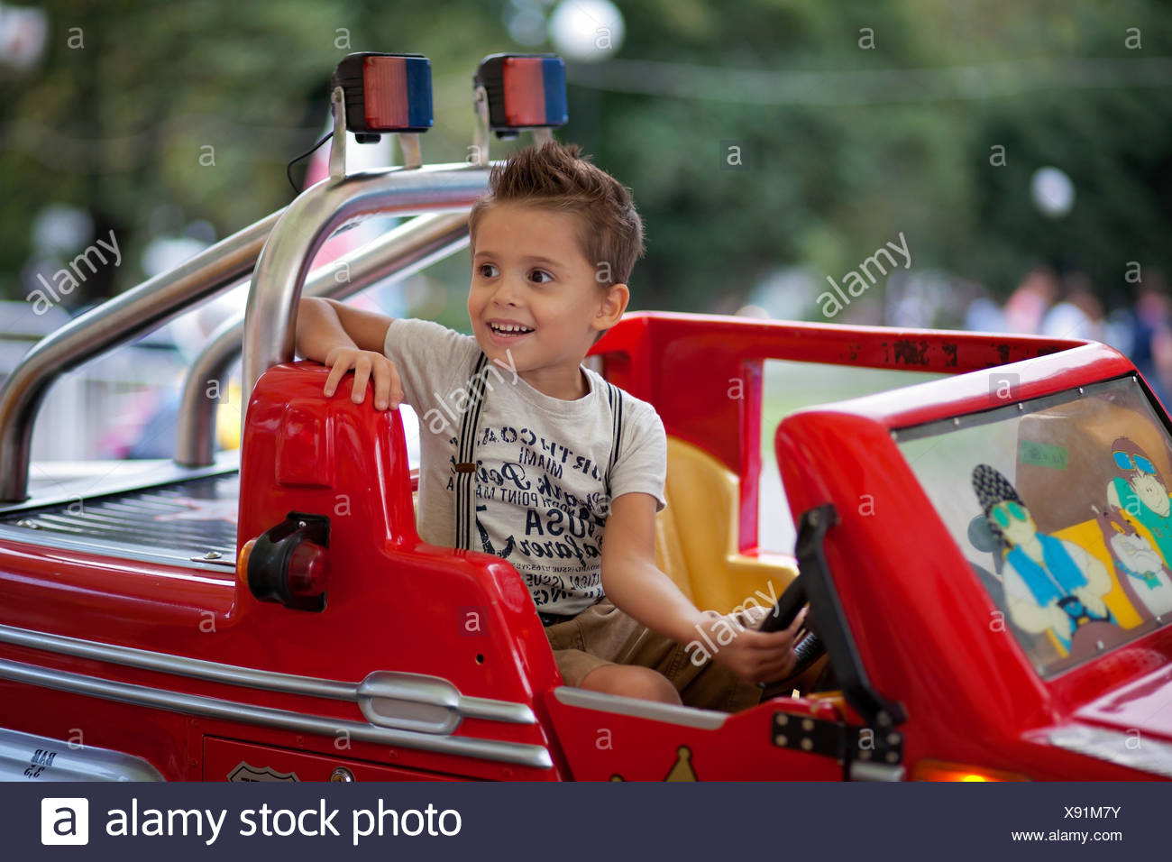 Boy (4-5) en voiture conduire amusement park Photo Stock