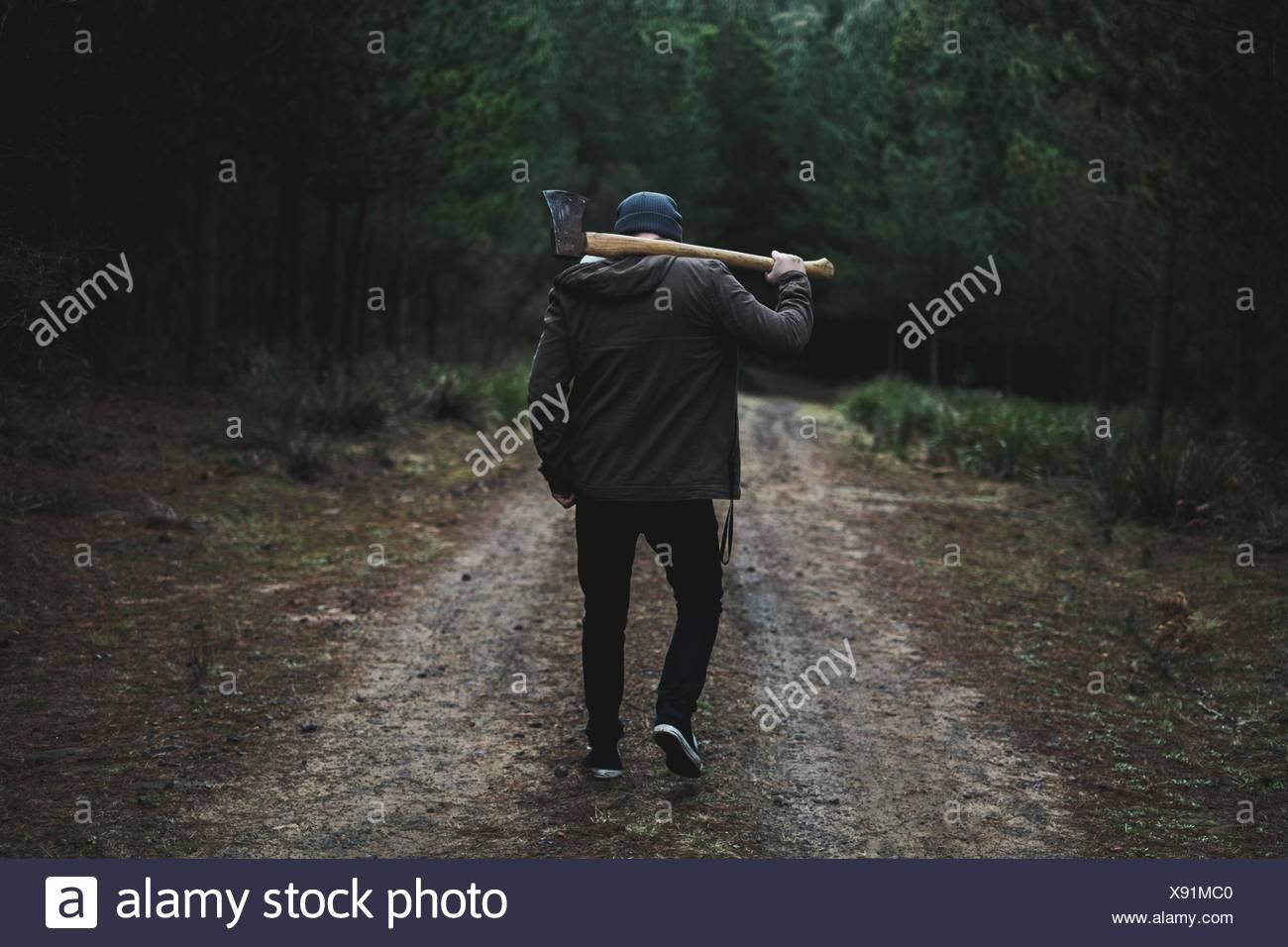 Vue arrière de l'homme avec l'Ax en forêt Photo Stock