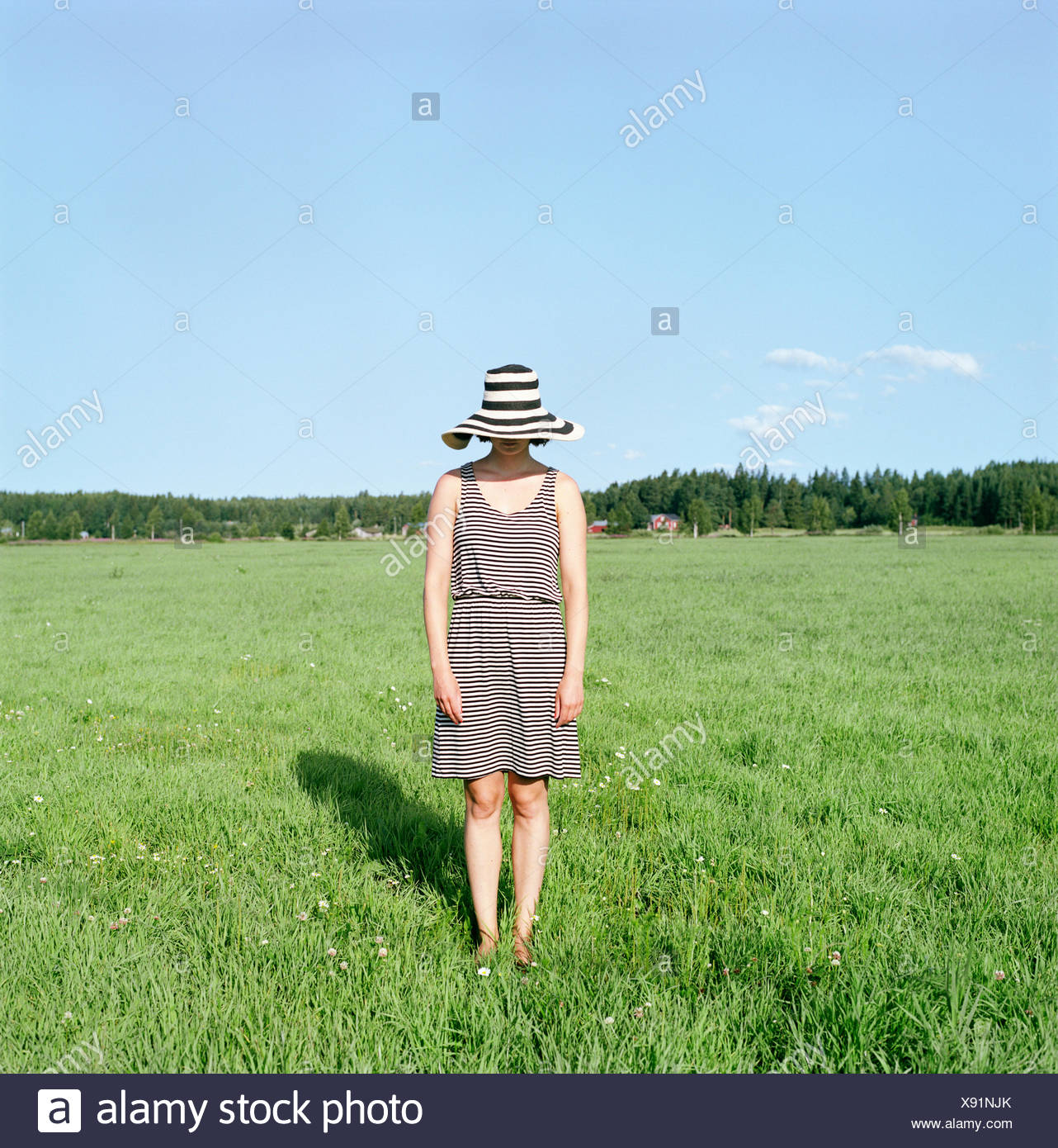 La Finlande, Uusimaa, Lapinjarvi, young woman wearing hat standing on grass Photo Stock