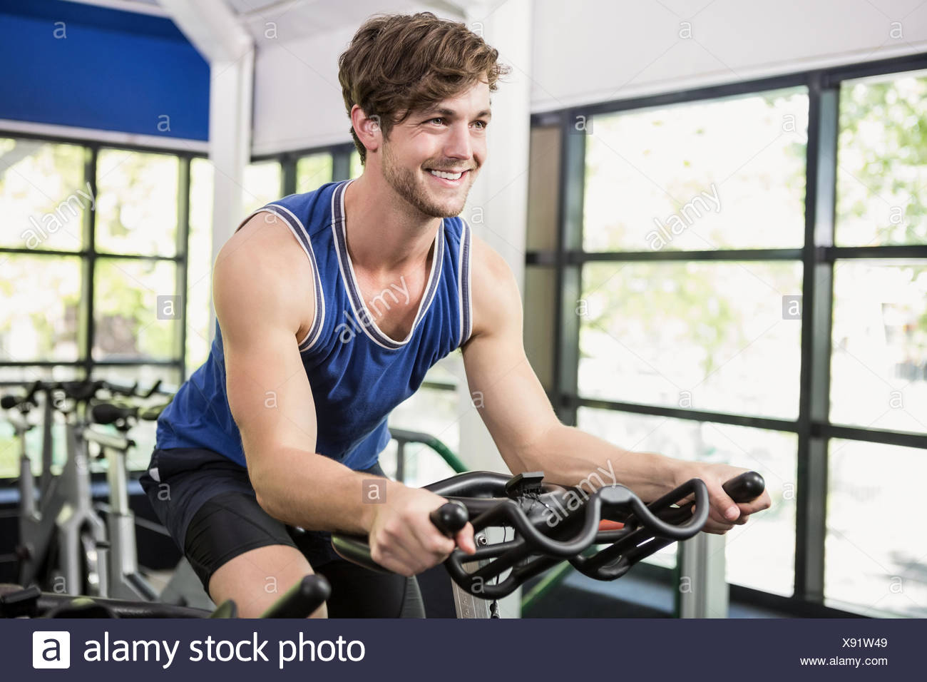 Man working out on exercise bike at spinning class Photo Stock