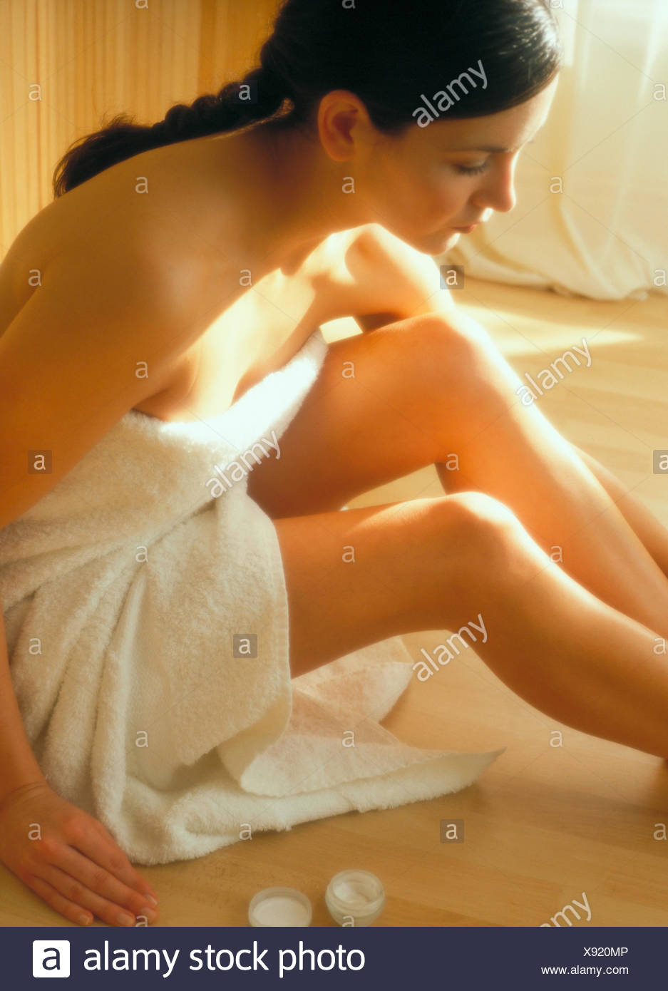 Woman sitting on floor appliquant la crème hydratant Photo Stock