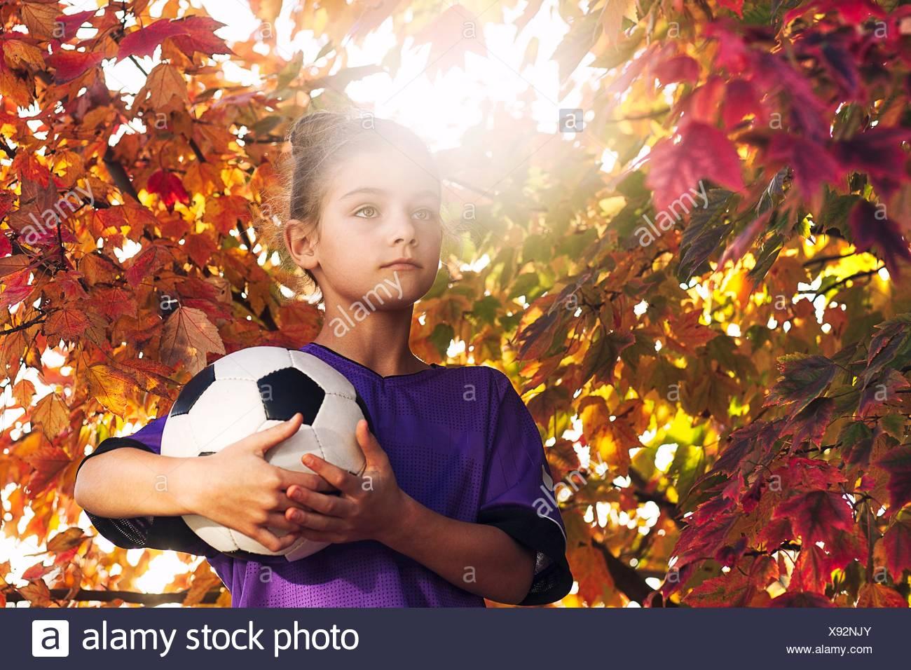 Les filles par arbre couvert de feuilles d'automne holding football looking away Photo Stock