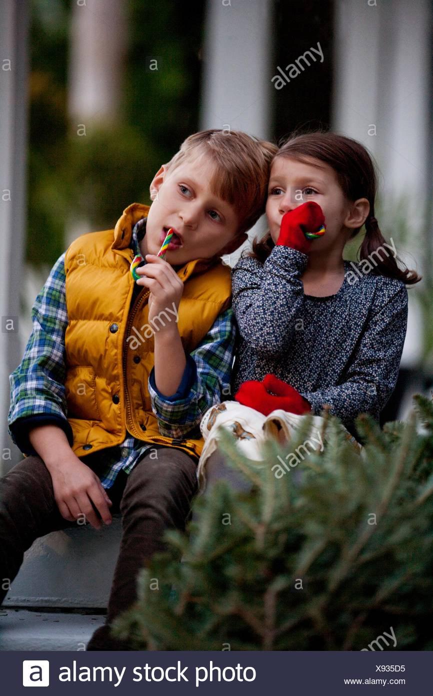 Portrait d'un garçon et fille manger des bonbons de fête Photo Stock