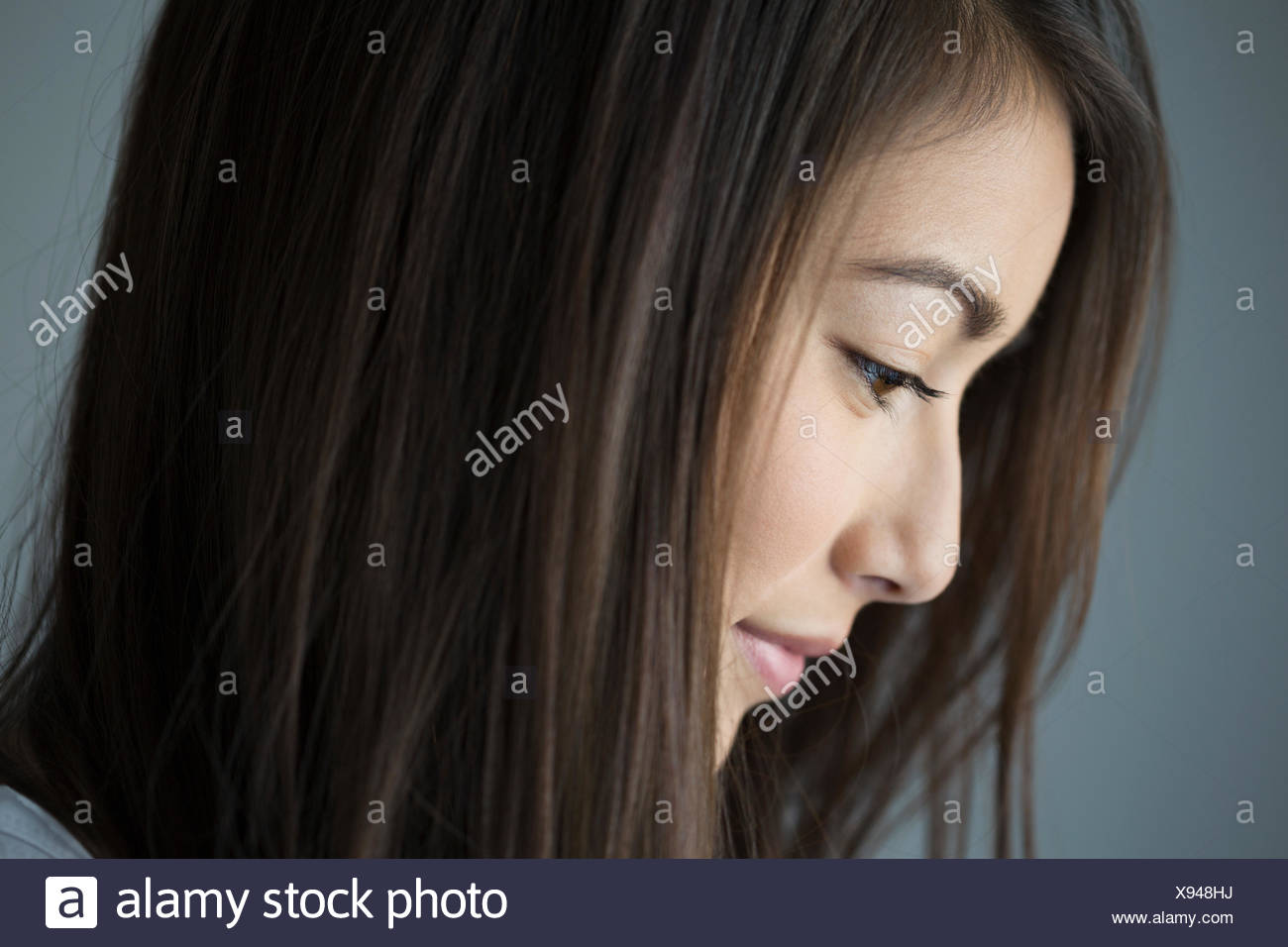 Close up profile pensive brunette woman looking down Photo Stock