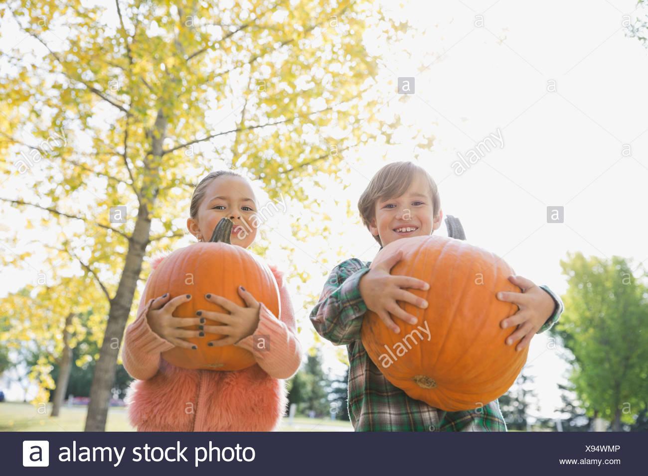Portrait d'enfants transportant des citrouilles Photo Stock