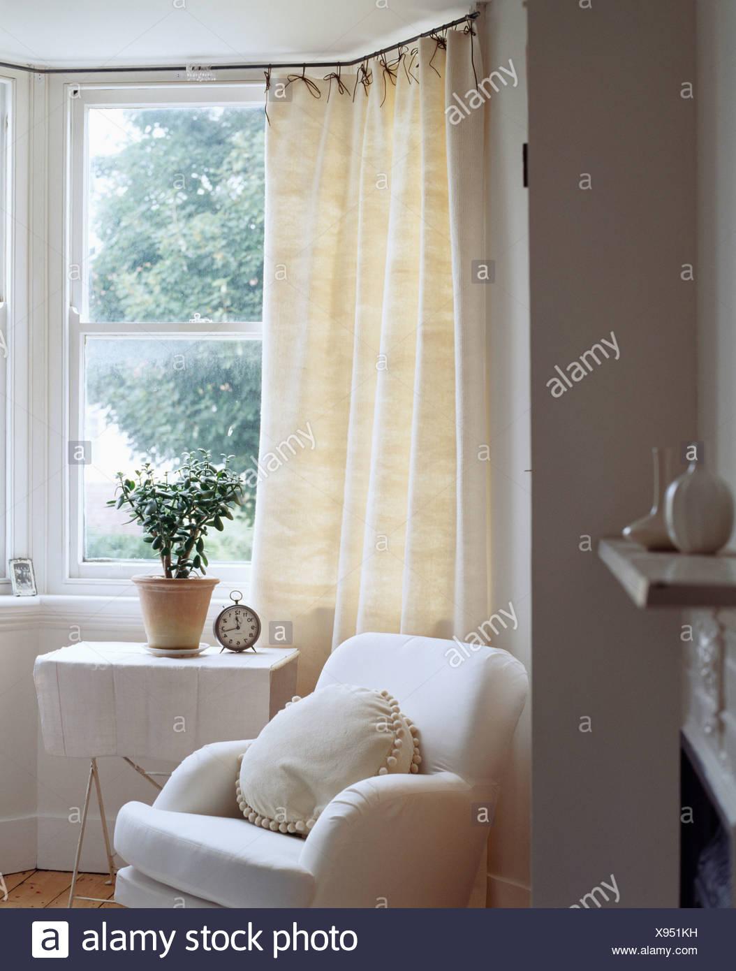 Rideau Sur Baie Vitrée fauteuil blanc et petite table avec un tissu blanc en face