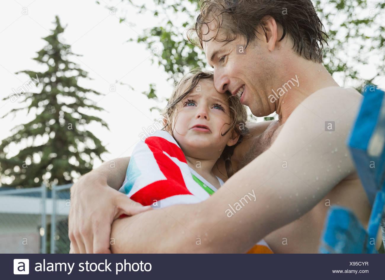 Consolante homme fille pleurer à la piscine Photo Stock