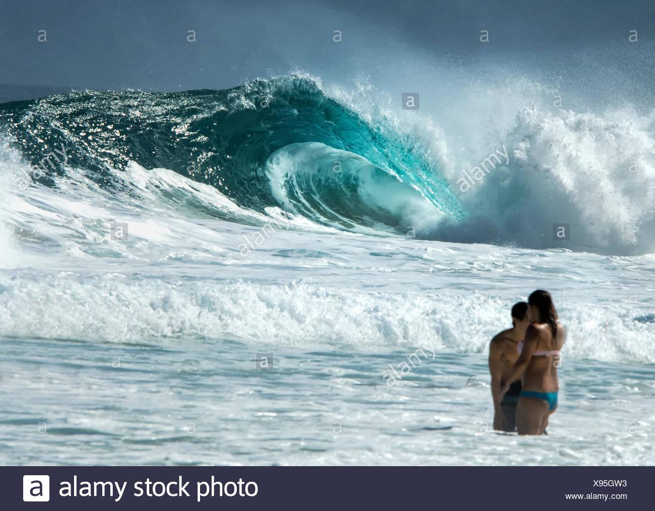 Personnes debout dans l'océan et d'énormes vagues de l'océan en arrière-plan Photo Stock