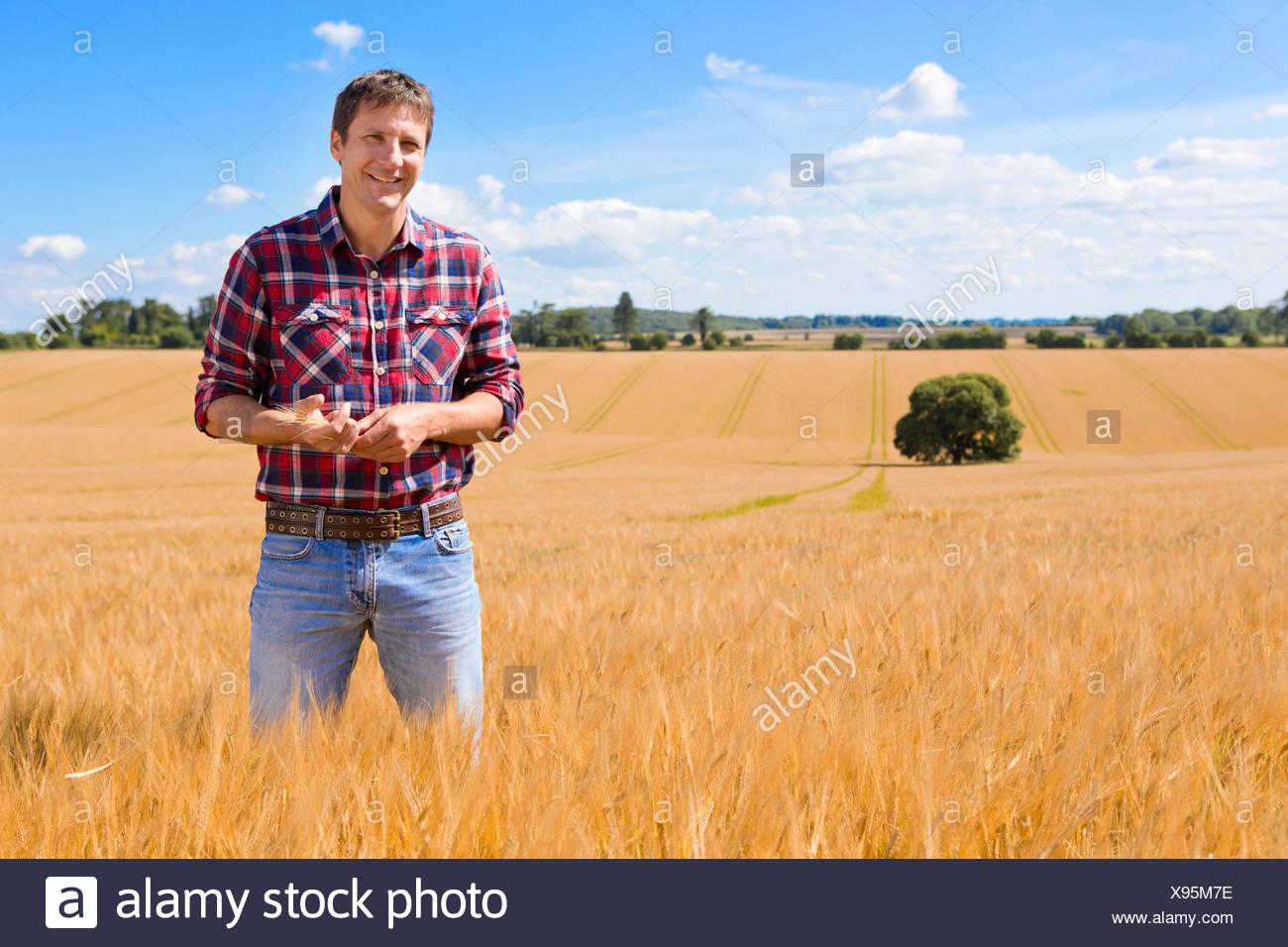 Portrait confiant agriculteur en milieu rural ensoleillée en été sur le terrain de la récolte d'orge Photo Stock