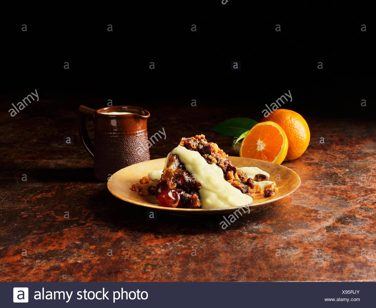 Le pudding de Noël avec la liqueur et sauce à l'orange sur la plaque d'or, les oranges, vintage pot de sauce Banque D'Images