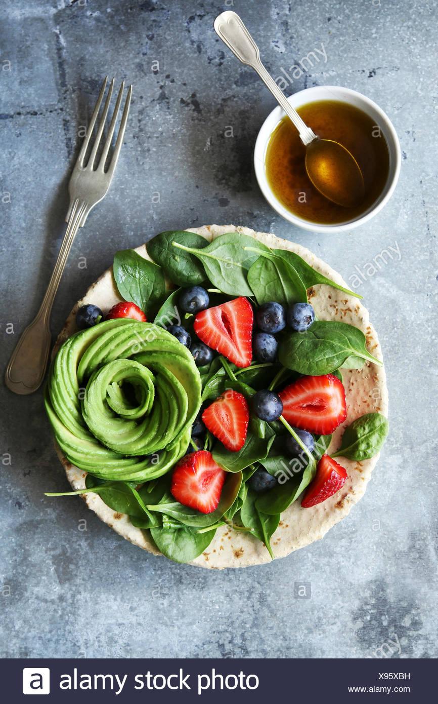 Mélange de salade aux épinards et petits fruits,rose avocat vinaigrette à la moutarde au miel.vue d'en haut Photo Stock