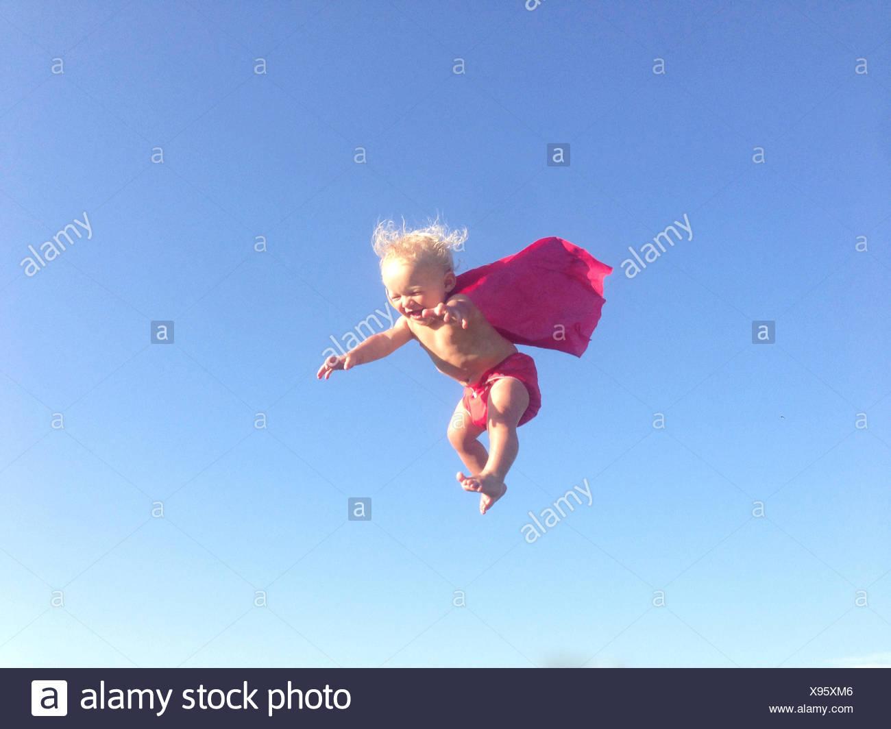 Bébé garçon habillé comme un super héros mid air Photo Stock