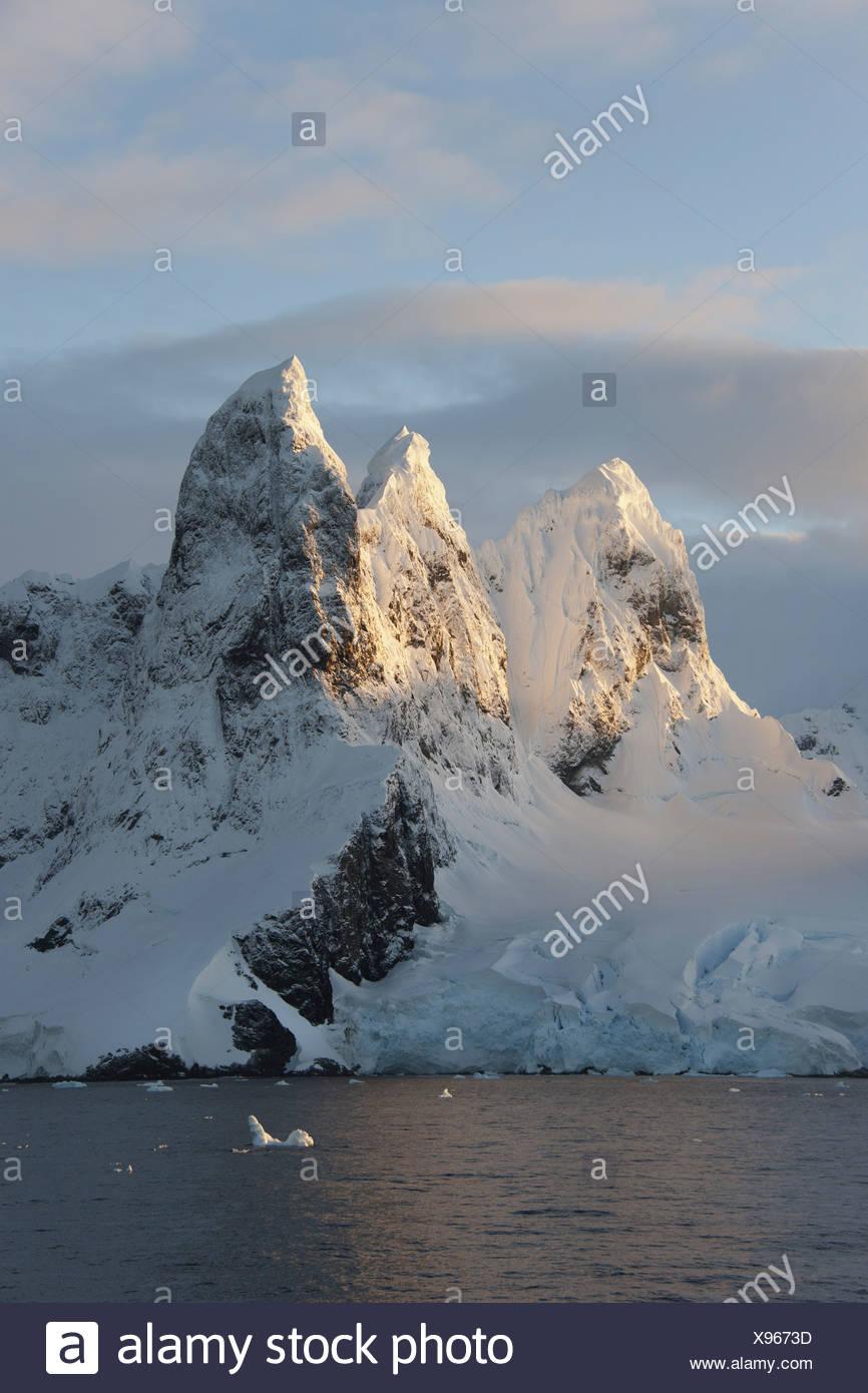 Lever du soleil sur les sommets des montagnes à l'entrée nord de la Canal Lemaire le long de la péninsule Antarctique Photo Stock